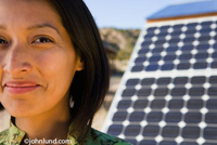 A Native American Indian woman with solar panels behind her in the background. The woman has short dark hair and a slight smile. She is looking at the camera and she is sharing the image with a solar panel array.